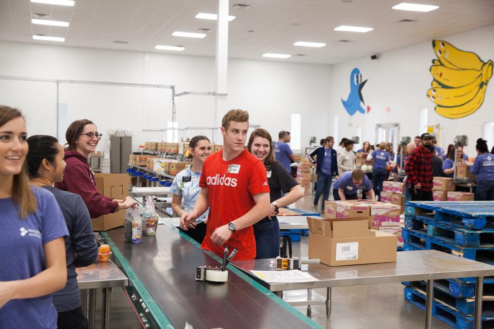 Misioneros voluntarios en el Central Texas Food Bank se muestran emocionados por la sorpresiva visita del élder Ulisses Soares, el 18 de octubre de 2019.