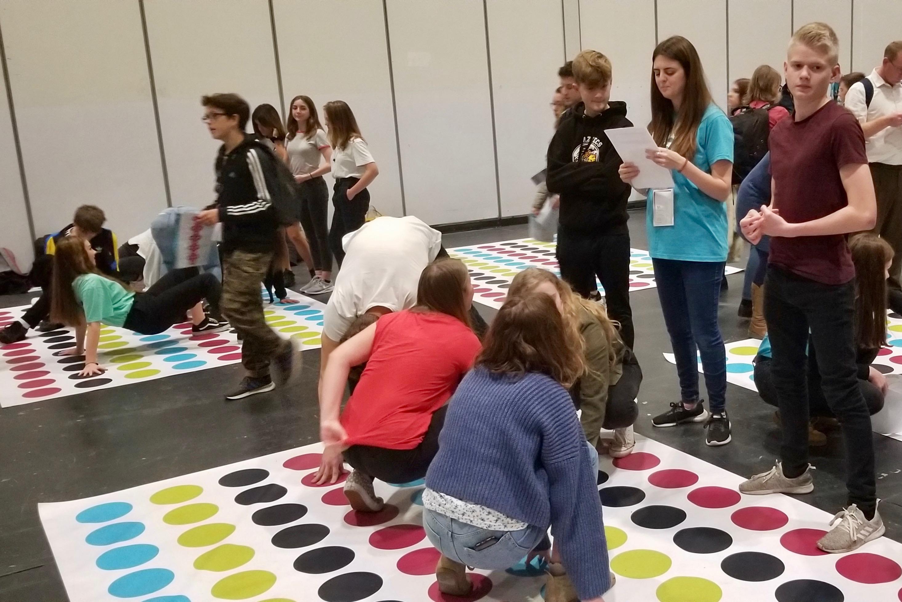 Unos jóvenes participan de un juego de Twister con temática de historia familiar, como parte de una actividad de descubrimiento del evento RootsTech Londres, el 26 de octubre de 2019.