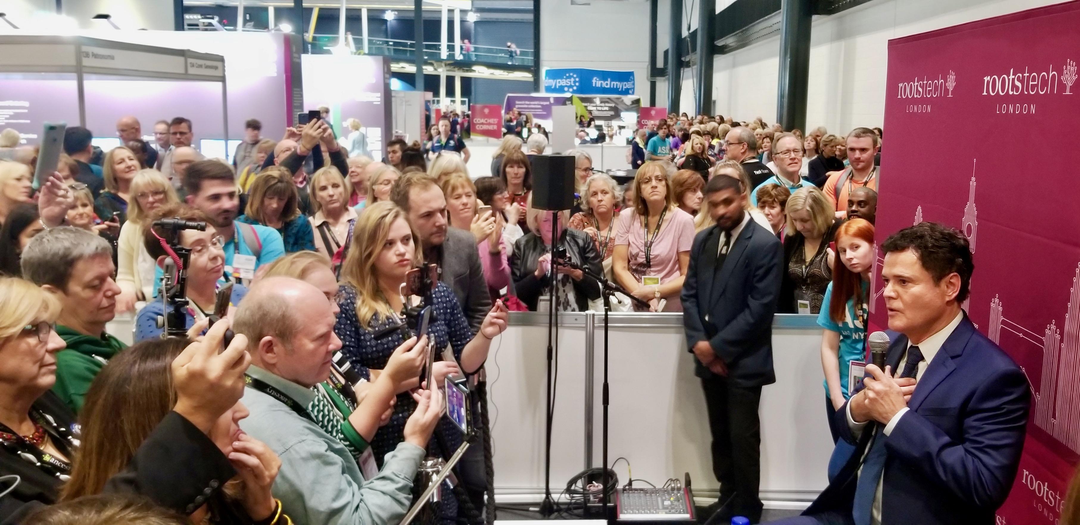 El animador santo de los últimos días, Donny Osmond (derecha), se reúne con los medios de comunicación en RootsTech Londres, el 26 de octubre de 2019, mientras una larga fila de participantes lo espera para conocerlo y saludarlo.