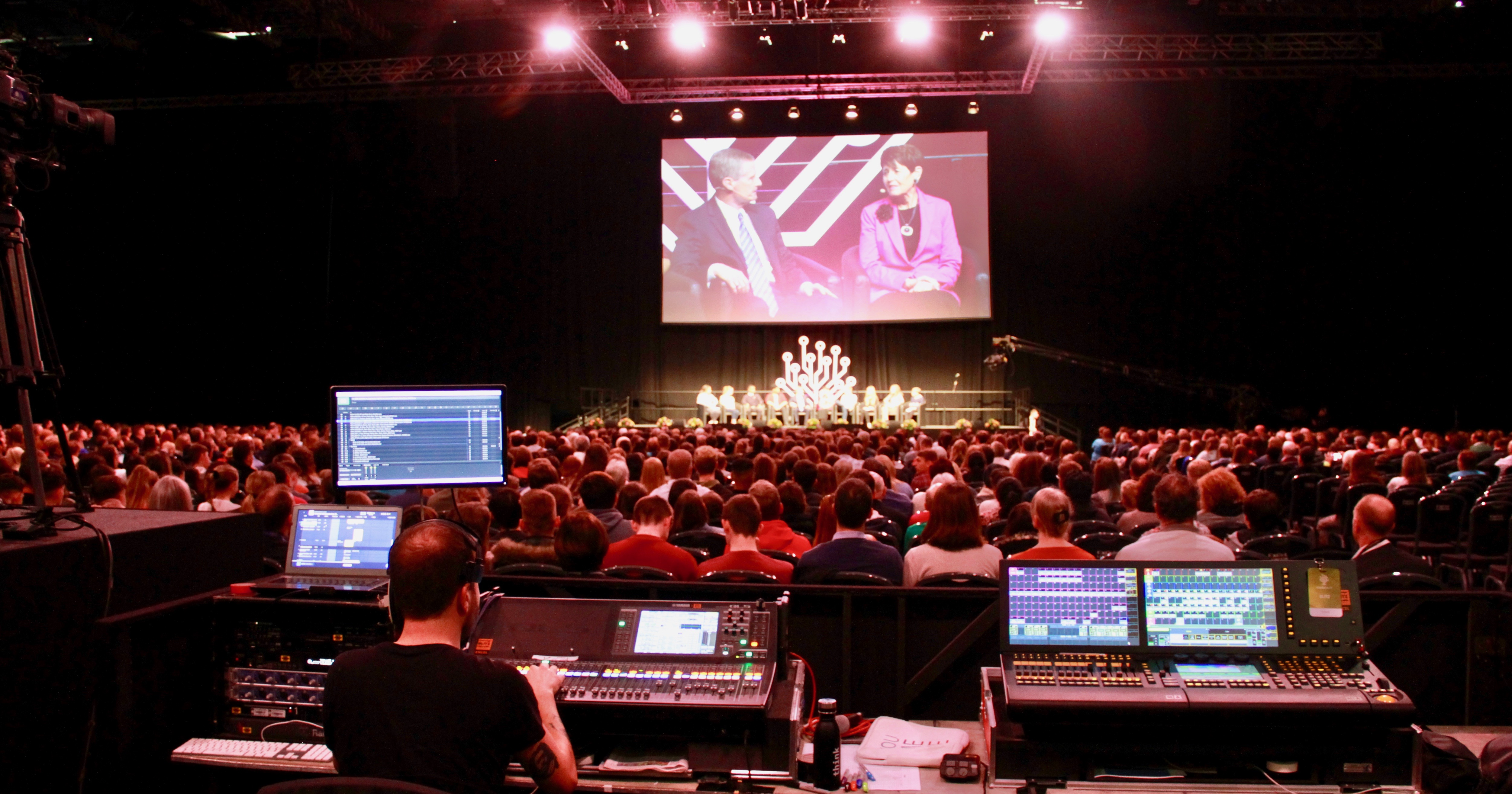 """El élder David A. Bednar y la hermana Susan Bednar aparecen en la pantalla mientras ocho jóvenes participan del panel de discusión """"Experiencia juvenil"""" con los Bednar durante el evento RootsTech Londres, el sábado 26 de octubre de 2019."""