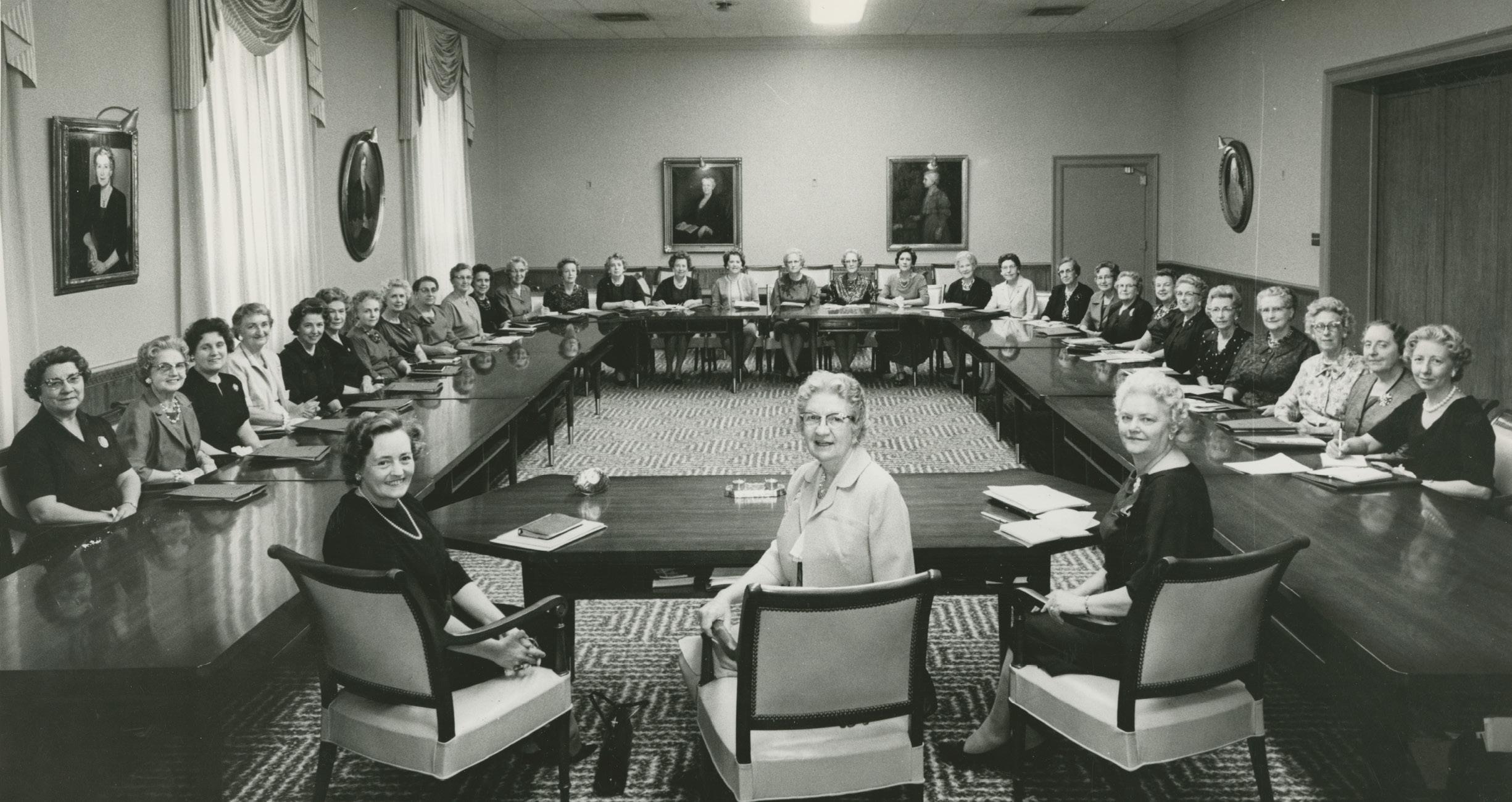 Las hermanas Belle S. Spafford, Marianne C. Sharp y Louise W. Madsen con la mesa general de la Sociedad de Socorro en 1962. Las miembros de la presidencia se ubican a la cabeza de la mesa. De izquierda a derecha: las hermanas Madsen, Spafford y Sharp y la mesa general de la Sociedad de Socorro, posan para una foto en el Edificio de la Sociedad de Socorro, que en ese entonces tenía 6 años. Las miembros de la mesa capacitaron a las unidades de la Sociedad de Socorro en todo el mundo, supervisaron la producción de ropa del templo, publicaron la Revista de la Sociedad de Socorro y crearon una currícula de la Sociedad de Socorro. Fotografía por J. M. Heslop.