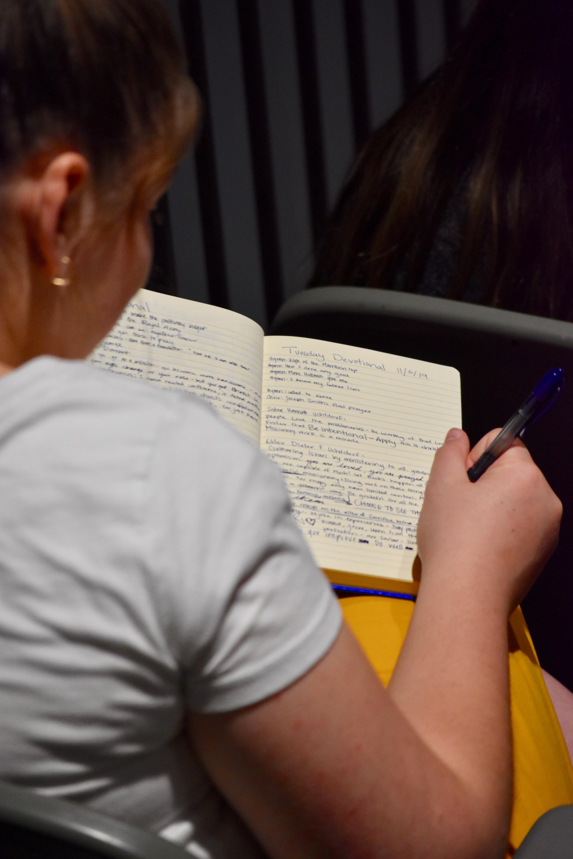 Una misionera toma notas en su diario durante un devocional con el élder Dieter F. Uchtdorf en el Centro de Capacitación Misional de Provo, el 5 de noviembre de 2019.