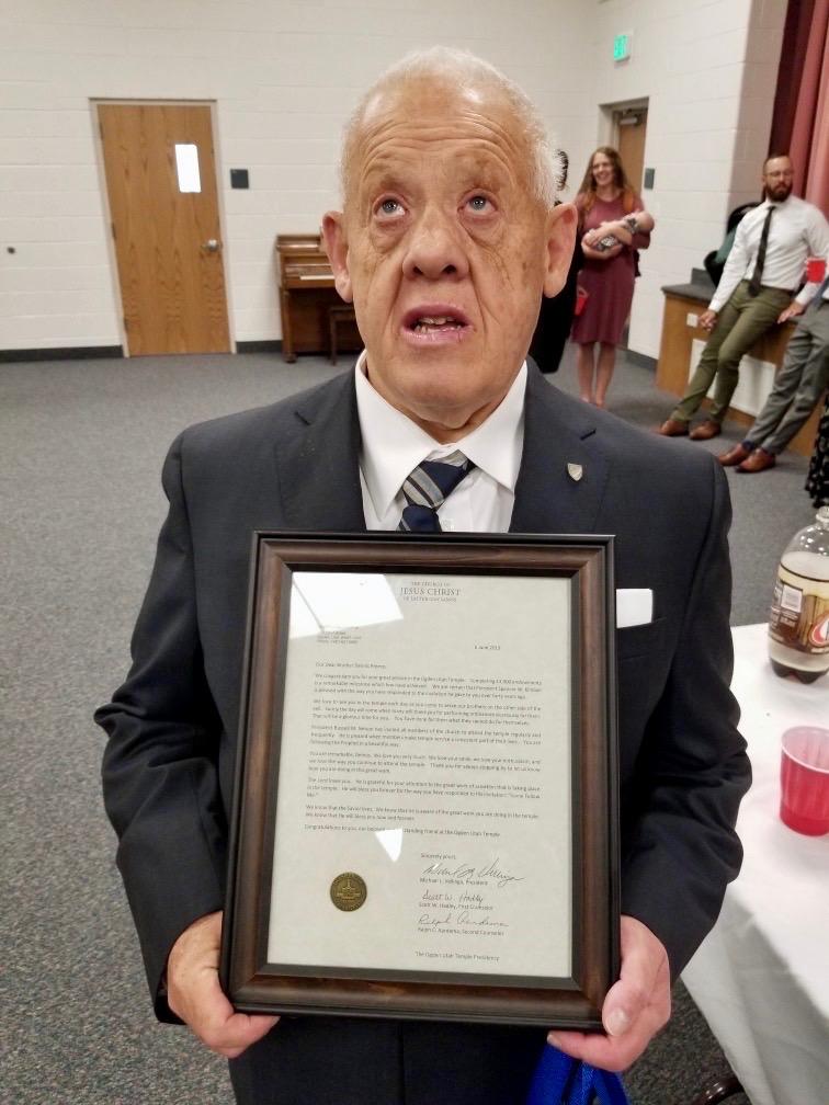 Dennis Preece sostiene una carta enmarcada de parte de la presidencia del Templo de Ogden en la que se lo reconoce por haber alcanzado las 13 000 investiduras en junio de 2019.