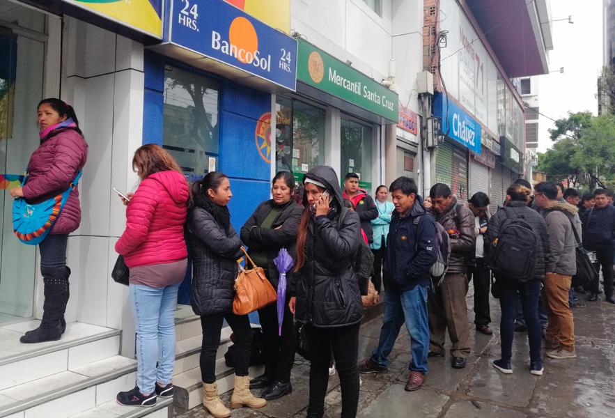 Personas hacen fila para usar cajeros automáticos en medio de protestas en La Paz, Bolivia, el lunes 11 de noviembre de 2019. La renuncia del presidente Evo Morales, el 10 de noviembre, deja un vacío de poder en un país dividido por protestas en contra y a favor de su gobierno. (AP Photo/Paola Flores)