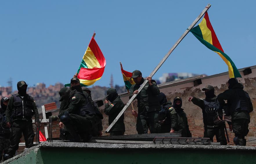 Policías en el techo de una estación de policía agitan banderas del país a solo unos metros de distancia del palacio presidencial, en La Paz, Bolivia, el sábado 9 de noviembre de 2019. Policías que resguardaban el exterior del palacio presidencial en La Paz se replegaron a sus barracas el sábado, mientras oficiales en otras ciudades bolivianas se han amotinado y unido a las protestas en contra del presidente Evo Morales, quien enfrentó dos semanas de disturbios por los disputados resultados de las elecciones. (AP Photo/Juan Karita)