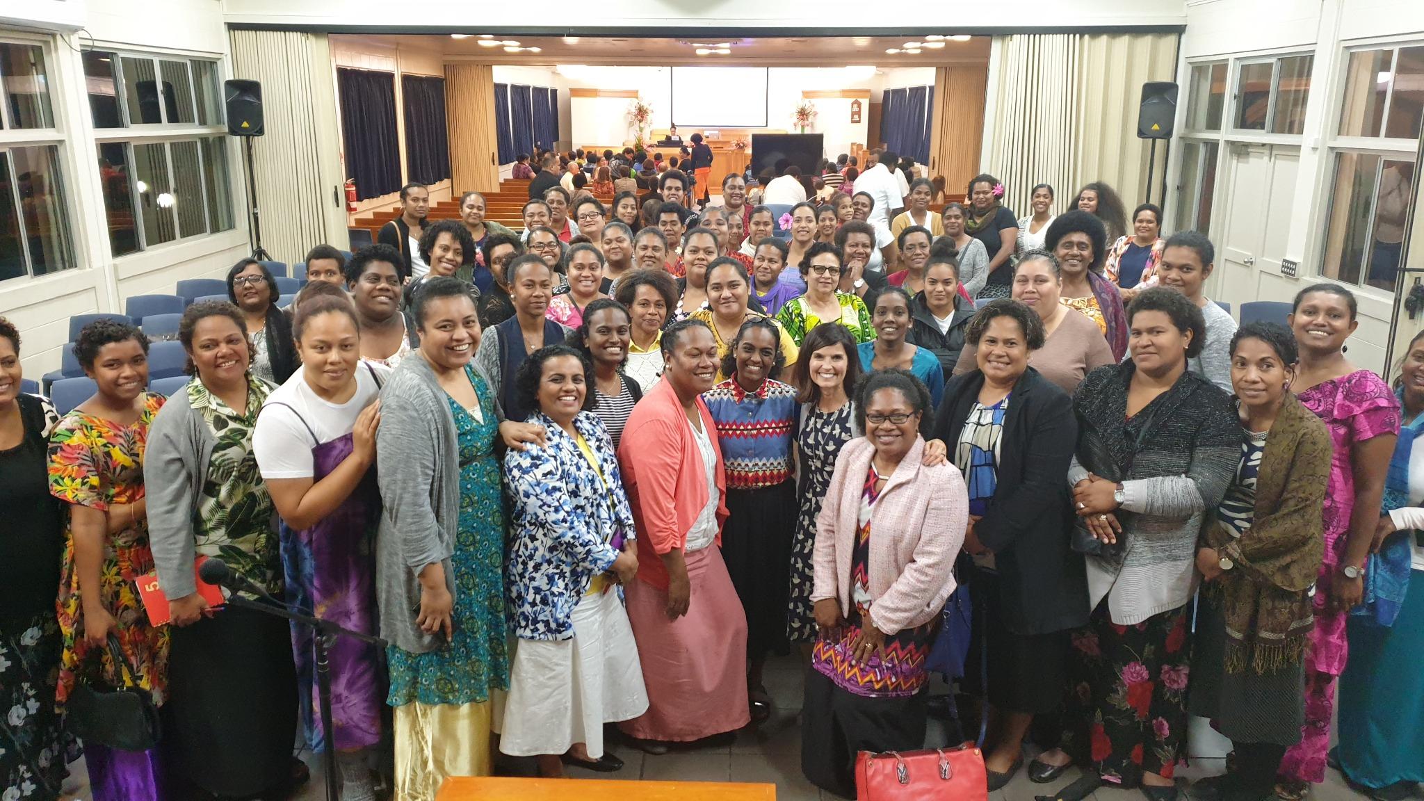 La hermana Becky Craven (al centro a la derecha) posa con un grupo de mujeres luego de un devocional en Fiyi. La hermana Craven visitó Fiyi junto a la hermana Sharon Eubank durante un viaje al Área Pacífico, en octubre de 2019.