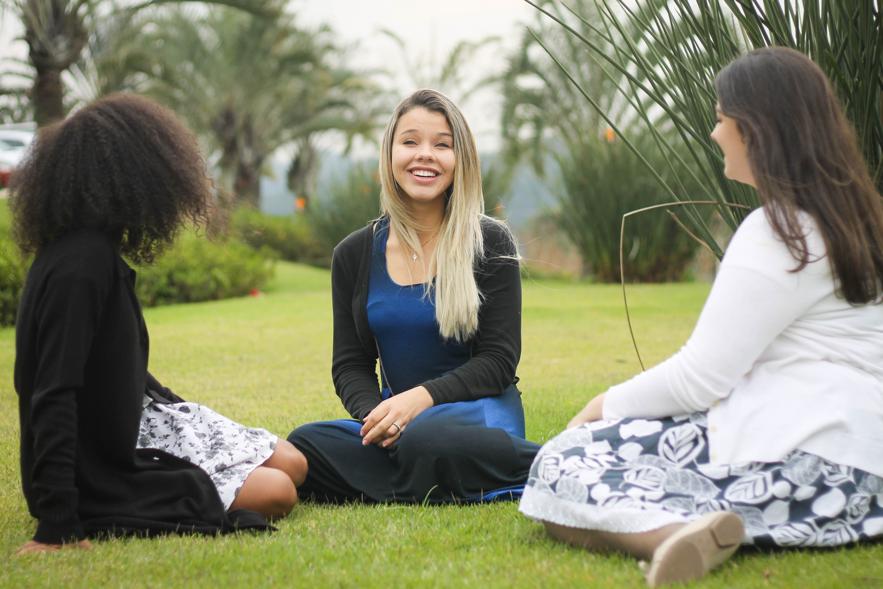 Mujeres jóvenes conversan sentadas sobre el césped. La Presidencia General de las Mujeres Jóvenes invita a todas las mujeres jóvenes a estudiar las doctrinas que se encuentran en el nuevo lema de las Mujeres Jóvenes, presentado en la conferencia general de octubre.