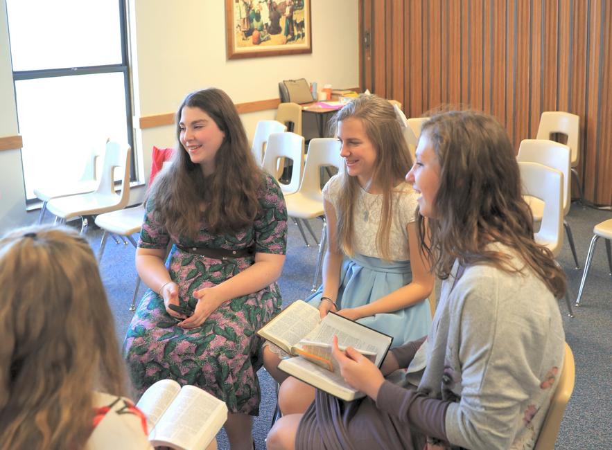 Mujeres jóvenes hablan sobre temas del evangelio que se encuentran en las escrituras durante una lección dominical.