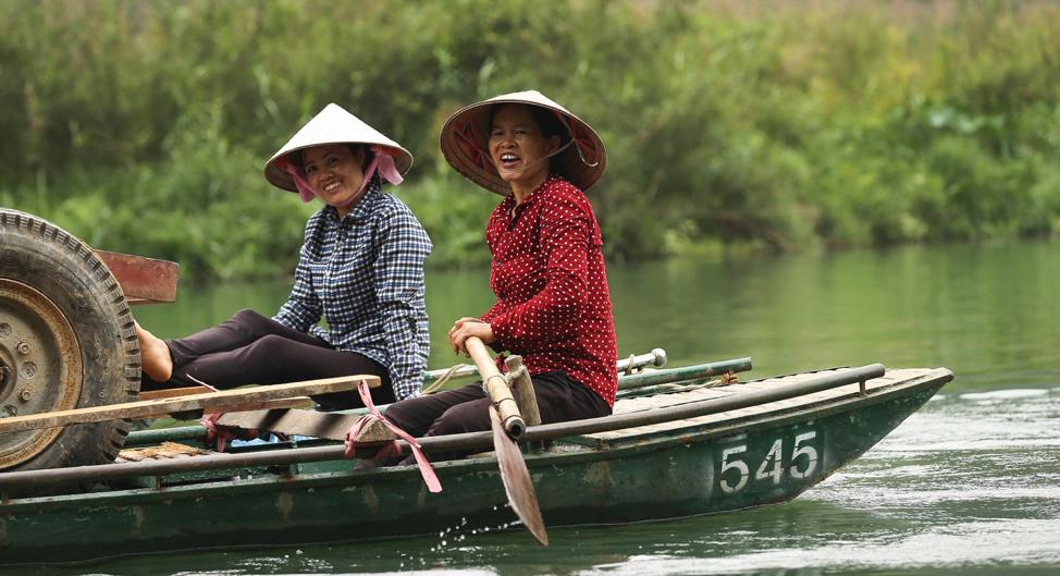 Unas mujeres sonríen mientras trabajan cerca de la aldea aborigen de Tràng An, Ninh Binh, Vietnam, el 23 de abril de 2018.
