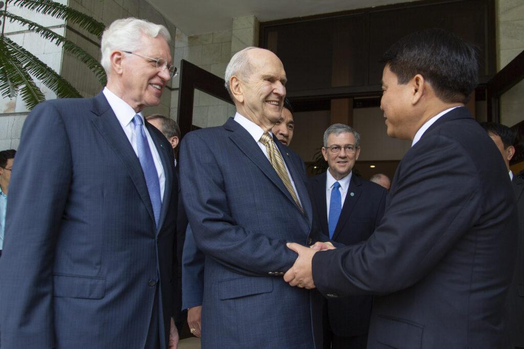 El presidente Russell M. Nelson y el élder D. Todd Christofferson saludan al alcalde de Hanói, Nguyen Duc Chung, el lunes 18 de noviembre de 2019.