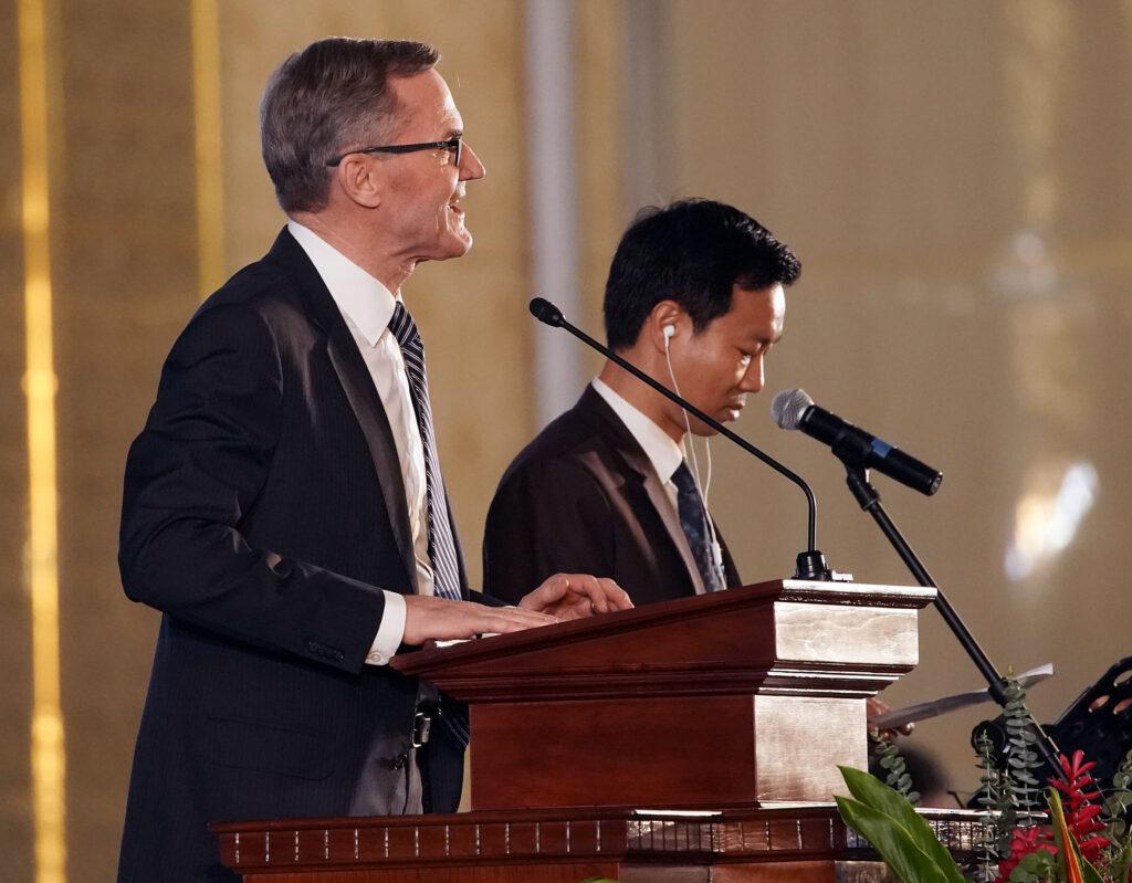 El élder Peter F. Meurs (izquierda), un setenta autoridad general que sirve en la presidencia del Área Asia de La Iglesia de Jesucristo de los Santos de los Últimos Días, habla por medio de un intérprete durante un devocional en Nom Pen, Camboya, el martes 19 de noviembre de 2019.