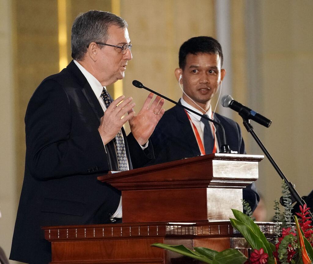 El élder David F. Evans (izquierda), un setenta autoridad general y presidente del Área Asia de La Iglesia de Jesucristo de los Santos de los Últimos Días, habla durante un devocional en Nom Pen, Camboya, el martes 19 de noviembre de 2019.