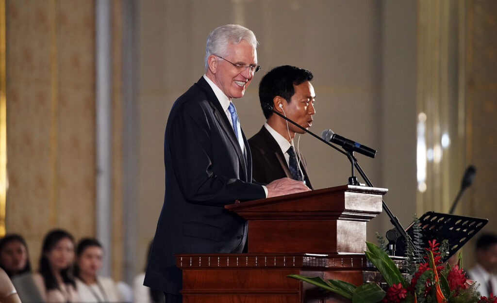 El élder D. Todd Christofferson (izquierda), del Cuórum de los Doce Apóstoles de La Iglesia de Jesucristo de los Santos de los Últimos Días, habla por medio de un intérprete durante un devocional en Nom Pen, Camboya, el martes 19 de noviembre de 2019.