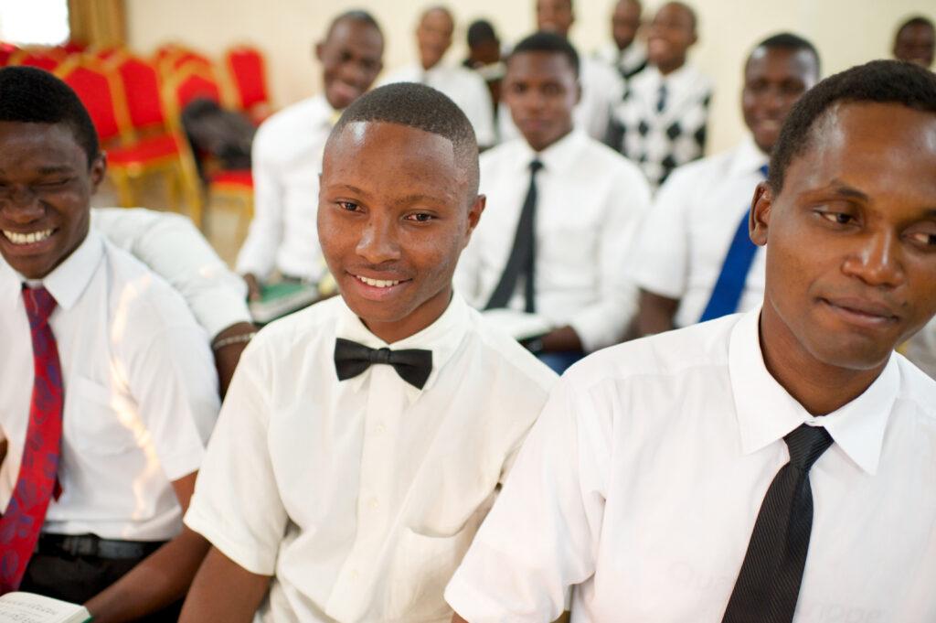 Un grupo de hombres jóvenes en la República Democrática del Congo sonriendo durante una reunión de cuórum. La Iglesia publicó recientemente un lema para los cuórums del Sacerdocio Aarónico.