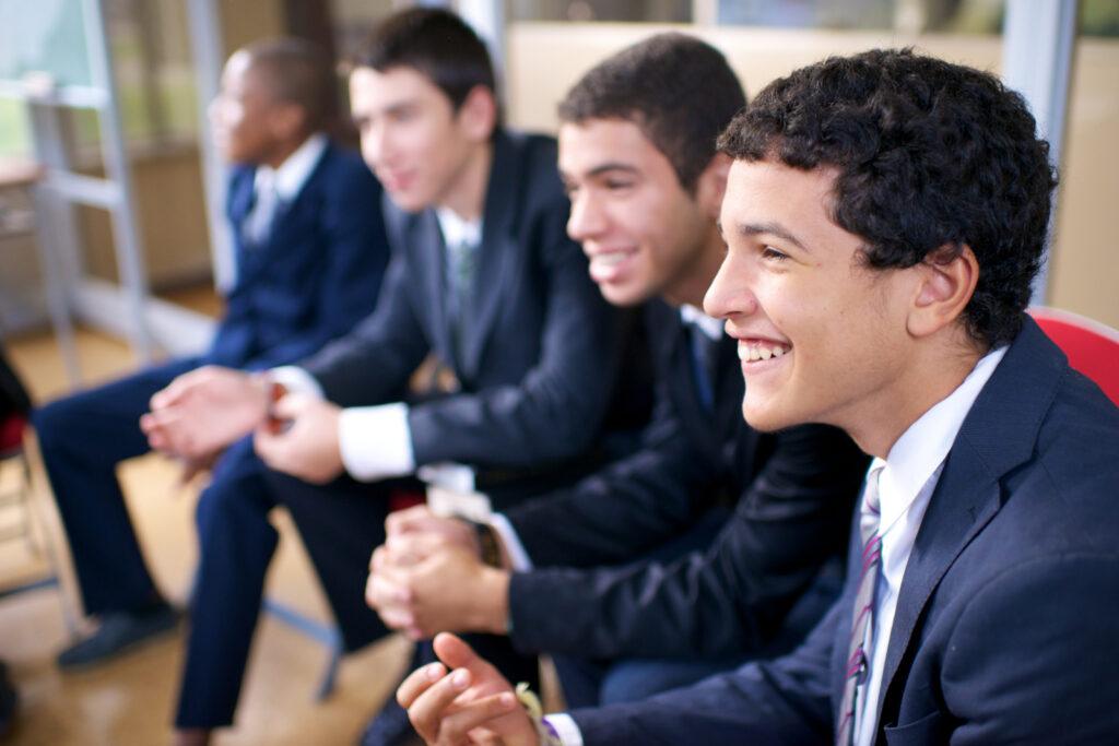 Un grupo de hombres jóvenes en Portugal sonriendo durante una reunión de cuórum. La Iglesia publicó recientemente un lema para los cuórums del Sacerdocio Aarónico.