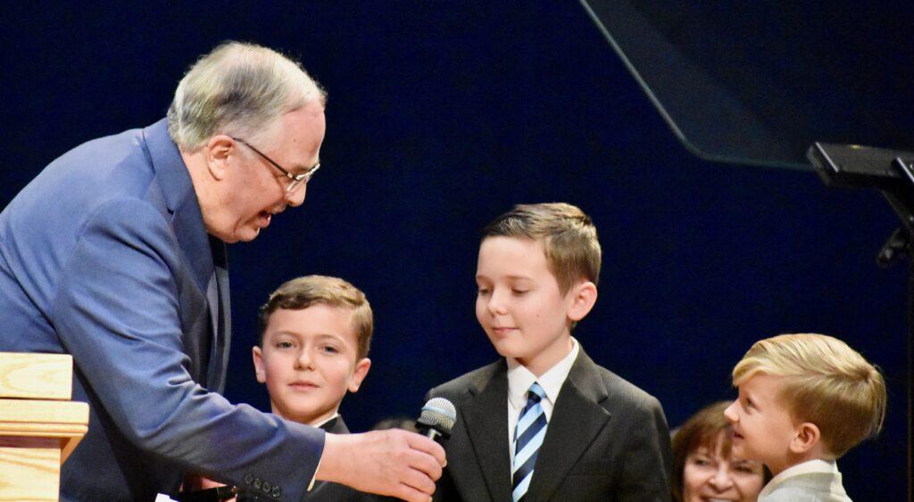 El élder Neil L. Andersen junto a varios de sus nietos durante un devocional del Día de Acción de Gracias en el Centro de Capacitación Misional de Provo, el 28 de noviembre de 2019, en Provo, Utah.