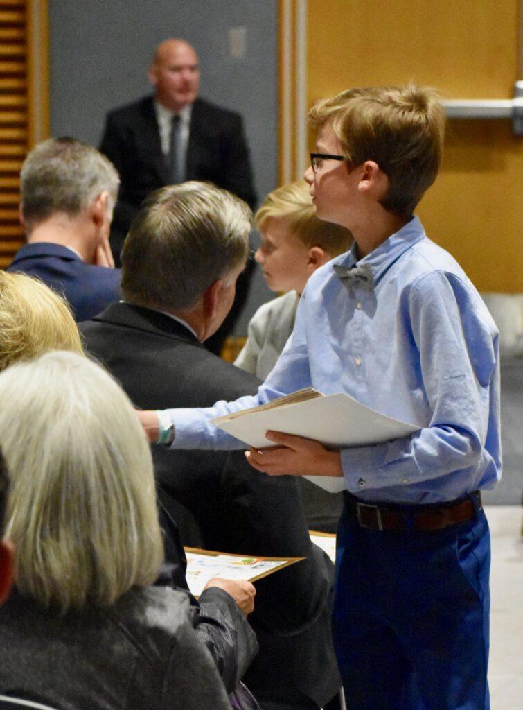 Nietos del élder Neil L. Andersen reparten una tarjeta de agradecimiento hecha por la familia, durante un devocional en el Centro de Capacitación Misional de Provo, el 28 de noviembre de 2019, en Provo, Utah.