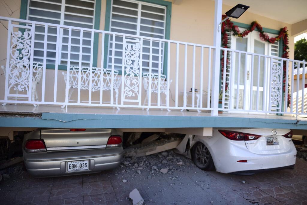Carros quedan aplastados bajo una casa que se derrumbó después de que un terremoto azotó a Guánica, Puerto Rico, el lunes, 6 de enero de 2020. Un terremoto de magnitud 5,8 azotó a Puerto Rico antes del amanecer el lunes, desencadenando pequeños deslizamientos y causando interrupciones eléctricas y grietas severas en algunas casas. No hubo informes inmediatos de heridos.