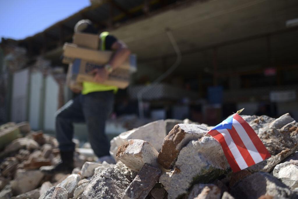 Una bandera de Puerto Rico permanece entre los escombros, luego de ser colocada allí donde los dueños de la tienda y sus familiares están ayudando a remover los suministros de la ferretería Ely Mer Mar, que se derrumbó parcialmente luego de que un terremoto sacudiera Guánica, Puerto Rico, el martes, 7 de enero de 2020. Un terremoto de magnitud 6,4 sacudió Puerto Rico el martes, antes del amanecer. Como resultado, murió un hombre, hubo varios heridos y se derrumbaron algunos edificios en la parte sur de la isla.