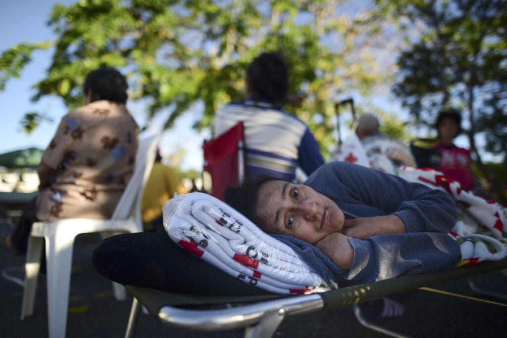 Maribel Rivera Silva, de 58 años, descansa fuera de un refugio con miedo de las posibles réplicas, luego de un terremoto en Guánica, Puerto Rico, el martes, 7 de enero de 2020. Un terremoto de magnitud 6,4 sacudió Puerto Rico el martes, antes del amanecer. Como resultado, murió un hombre, hubo varios heridos y se derrumbaron algunos edificios en la parte sur de la isla.