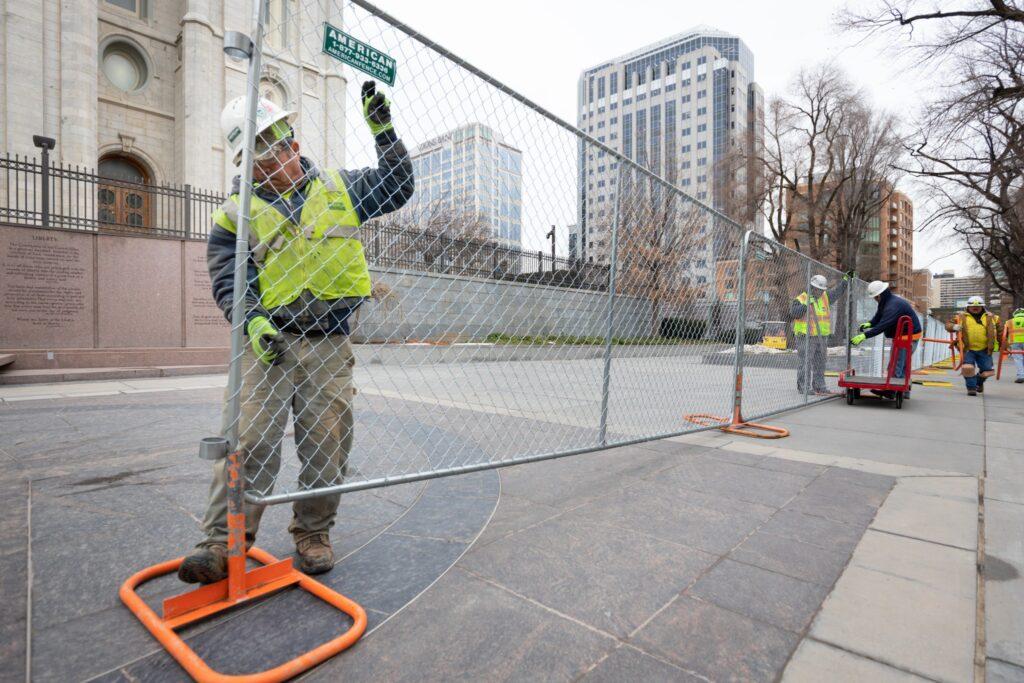 Los trabajadores instalan una cerca alrededor del Templo de Salt Lake al comenzar la renovación en la Manzana del Templo en Salt Lake City.