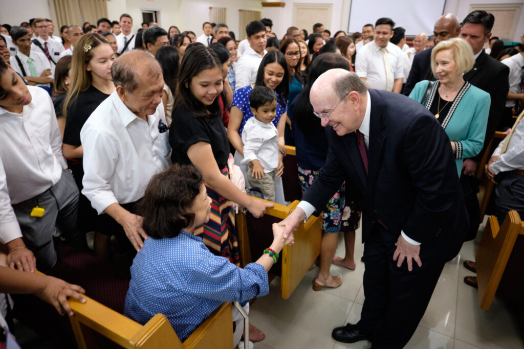 Élder Quentin L. Cook, del Cuórum de los Doce Apóstoles, y su esposa, Mary, saludan a Santos de los Últimos Días en el centro de reuniones de la Estaca Filipinas Mandaluyong, en Manila, el domingo, 12 de enero de 2020.