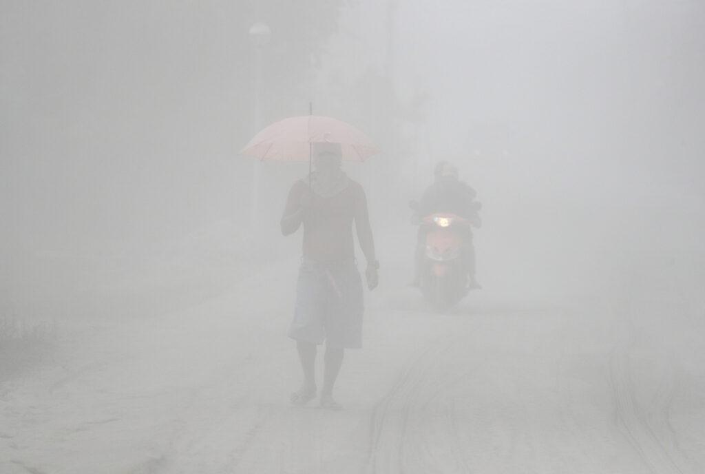 Un hombre camina entre una nube de ceniza volcánica al ser evacuado a terrenos seguros mientras erupciona el volcán Taal, en Tagaytay, provincia de Cavite, al sur de Filipinas, el lunes, 13 de enero de 2020. Lava roja hirviendo es arrojada por el volcán después de una súbita erupción de ceniza y vapor que obligó a los residentes a huir y a cerrar el aeropuerto de Manila, oficinas y escuelas.