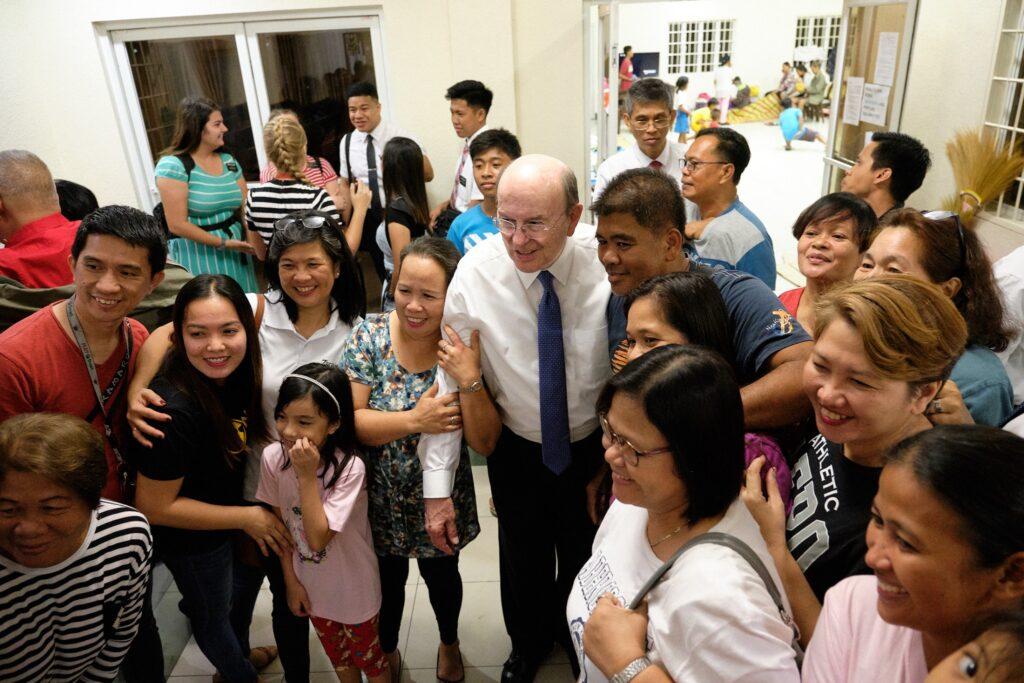 El élder Quentin L. Cook saluda a Santos de los Últimos Días reunidos en una capilla local al tiempo en que el volcán Taal continúa arrojando ceniza al sur de Manila, Filipinas.