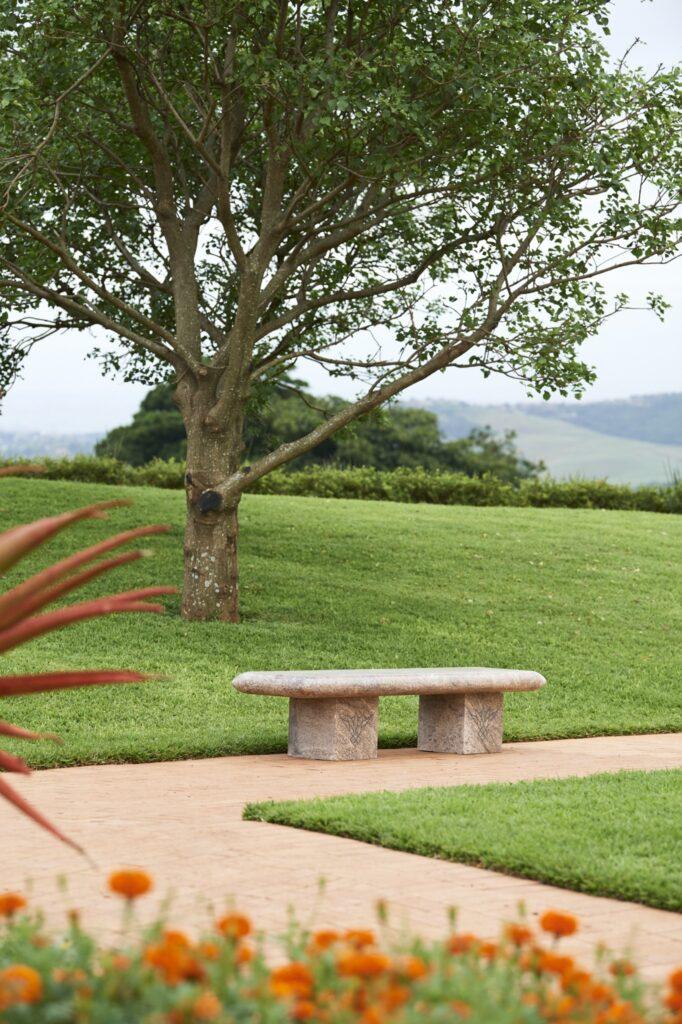 En los jardines, dotados de hermosos paisajes, hay bancos para sentarse, meditar y observar el Templo de Durban, Sudáfrica.