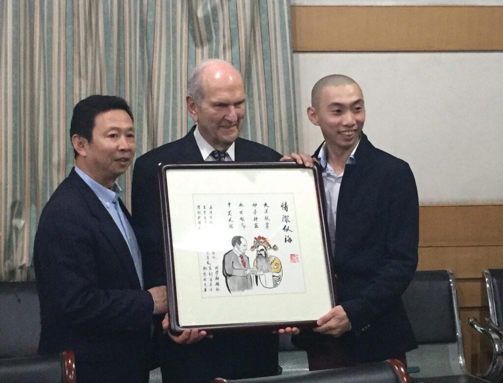 El presidente Russell M. Nelson recibe un homenaje en octubre de 2015 de parte del hijo y el nieto de Fang Rongxiang, la estrella de ópera china cuya vida él salvó con una cirugía de corazón.