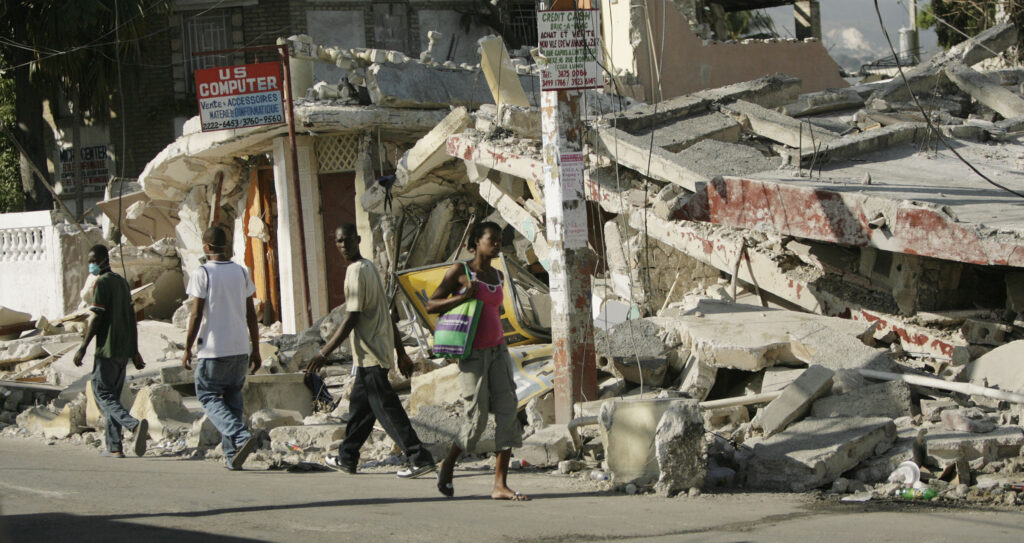 Haitianos caminan cerca de los escombros de los edificios derrumbados en Puerto Príncipe, Haití, el 19 de enero de 2010 — una semana después de que un terremoto de magnitud 7,0 azotara la región.