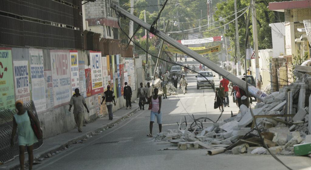 Haitianos caminan cerca de los escombros de las redes eléctricas y edificios derrumbados en Puerto Príncipe, Haití, el 19 de enero de 2010 — una semana después de que un terremoto de magnitud 7,0 azotara la región.