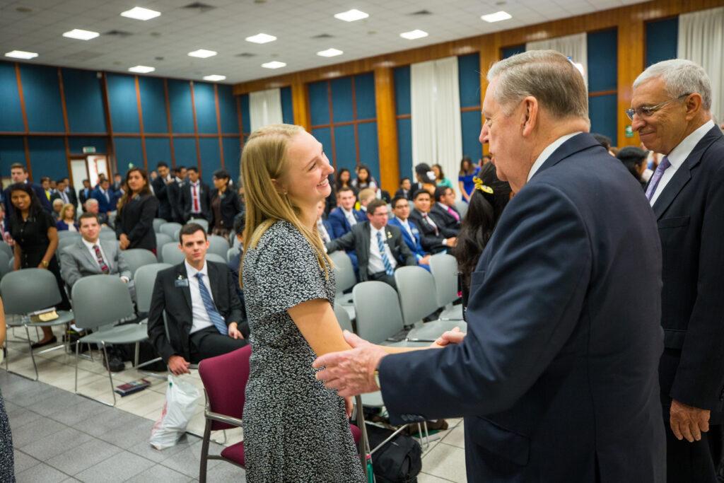El élder Jeffrey R. Holland saluda a una hermana misionera durante una reunión en Lima, Perú.