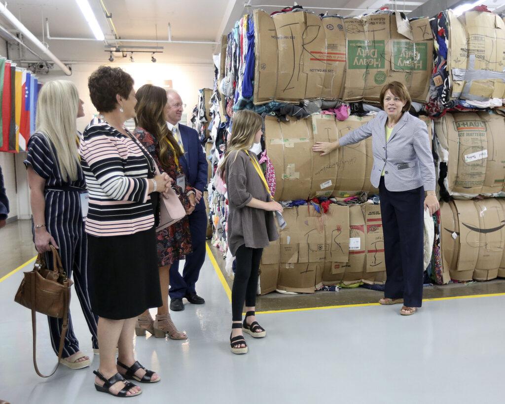 La hermana Sharon Eubank, primera consejera de la presidencia general de la Sociedad de Socorro, dirige un recorrido por las instalaciones del Centro Humanitario SUD para los cónyuges de los gobernadores de los Estados Unidos y habla sobre la donación de ropa en Salt Lake City el jueves, 25 de julio de 2019.