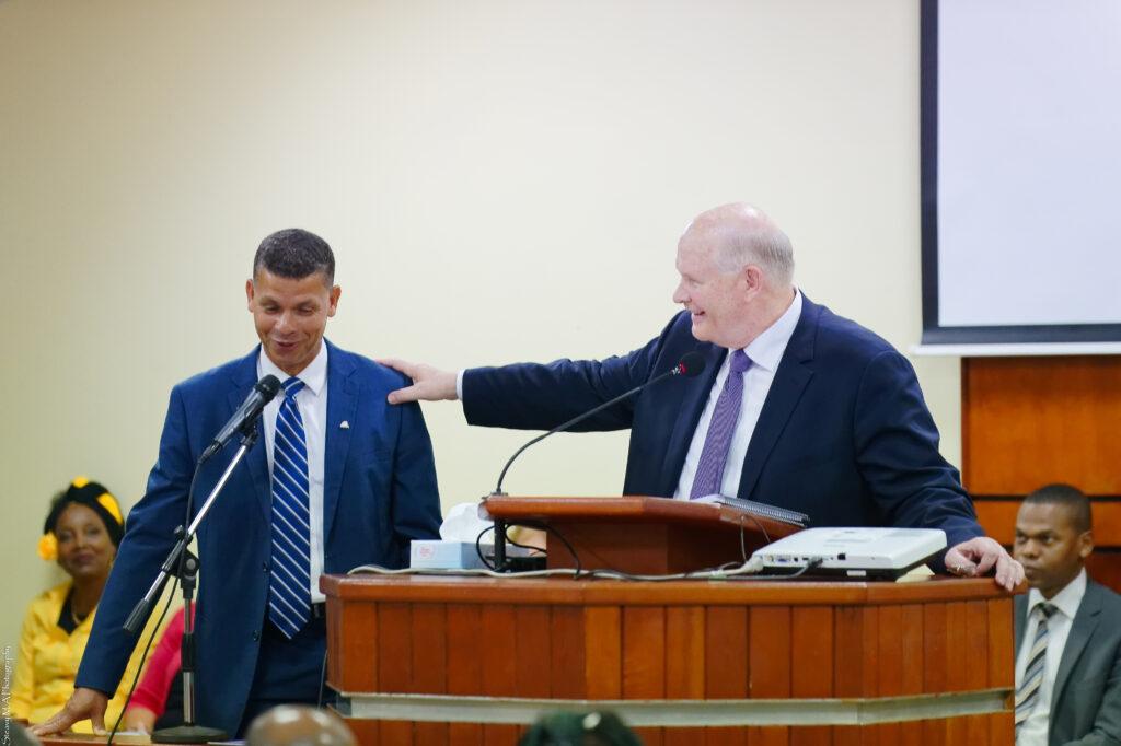 El élder Dale G. Renlund posa su mano en el hombro de un miembro, en el púlpito, durante una reunión con santos de los últimos días en Guadalupe, el 17 de febrero de 2020. La visita del apóstol a la isla fue parte de la revisión anual del Área Caribe.