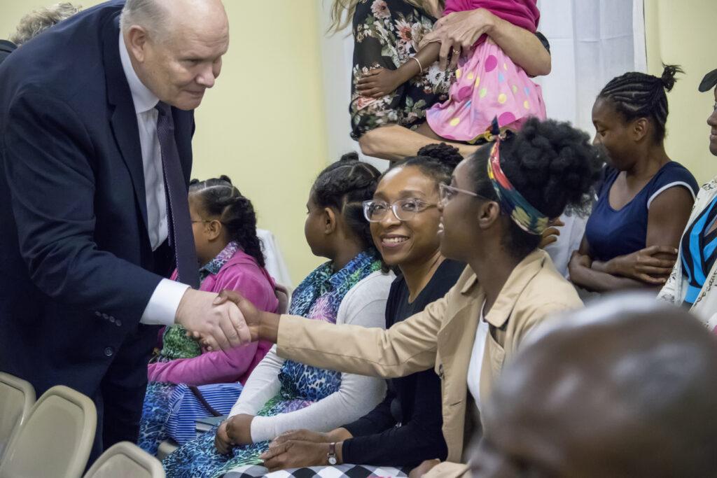 El élder Dale G. Renlund saluda a una mujer joven en Dominica, durante una visita al Área Caribe, el 16 de febrero de 2020.