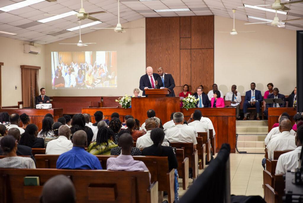 El élder Dale G. Renlund habla en el púlpito con un miembro durante una transmisión de una capacitación de liderazgo en Kingston, Jamaica, el 22 de febrero de 2020. El apóstol visitó la isla como parte de la revisión anual del Área Caribe.
