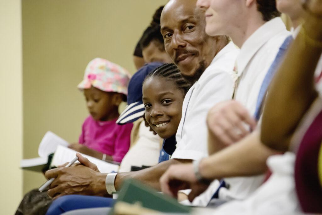 Miembros de la Iglesia en Dominica cantan en una reunión con el élder Dale G. Renlund, durante la visita del apóstol al Área Caribe el 16 de febrero de 2020.