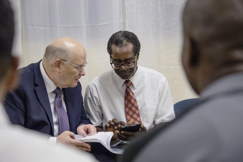 El élder Dale G. Renlund mira un manual con un miembro en Dominica, durante la visita del apóstol al Área Caribe el 16 de febrero de 2020.