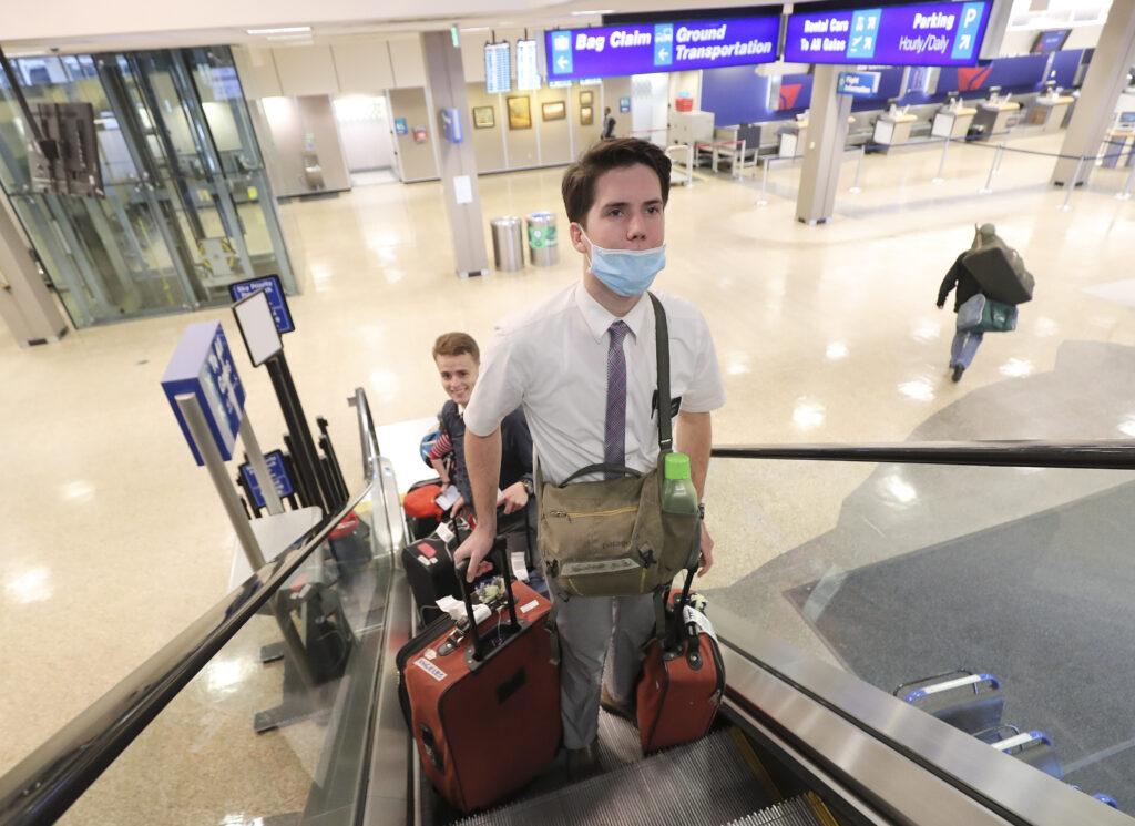 El élder Ethan Bird empuja su equipaje mientras cientos de misioneros de La Iglesia de Jesucristo de los Santos de los Últimos Días regresan de las Filipinas al Aeropuerto Internacional de Salt Lake City el domingo, 22 de marzo de 2020.